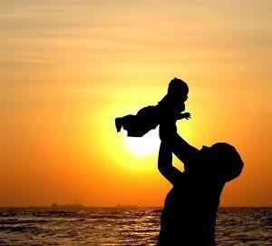 Fotografi: Barn holdes opp i været av foreldre, solnedgang i bakgrunnen.